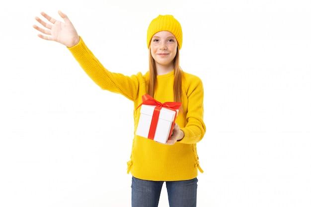 La piccola ragazza caucasica tiene una scatola bianca con il regalo e ha molte emozioni isolate su bianco.