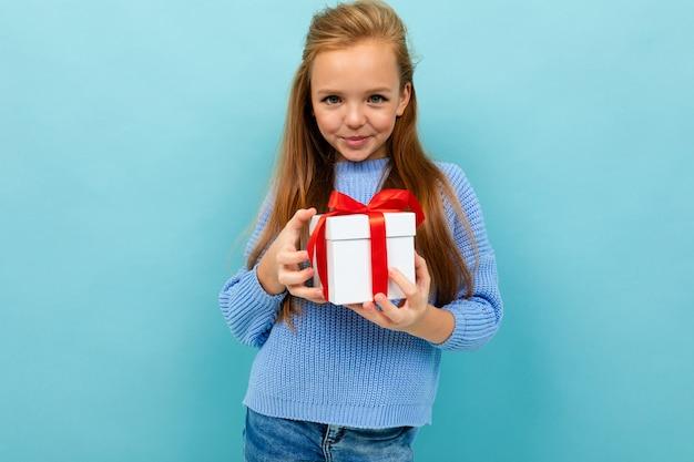 La piccola ragazza caucasica tiene una scatola bianca con il regalo e ha molte emozioni isolate su fondo blu