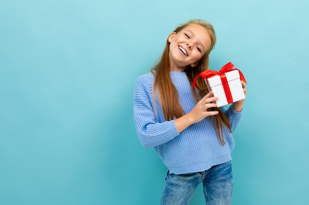 La piccola ragazza caucasica tiene una scatola bianca con il regalo e ha molte emozioni isolate sul blu