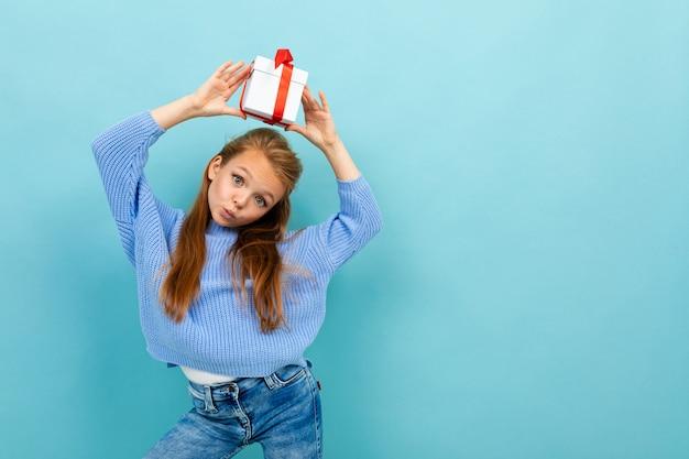 La piccola ragazza caucasica tiene una scatola bianca con il regalo sotto la sua testa e ha molte emozioni isolate sul blu