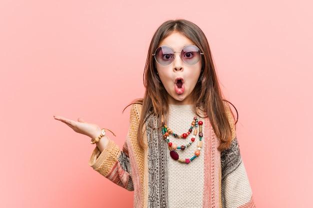 La piccola ragazza di hippy ha impressionato lo spazio della copia della tenuta sulla palma.
