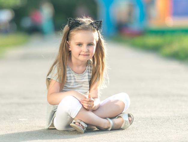 La piccola ragazza felice è seduta