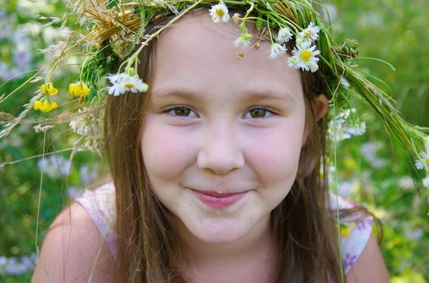 La piccola ragazza felice in una ghirlanda di campo fiorisce nel prato