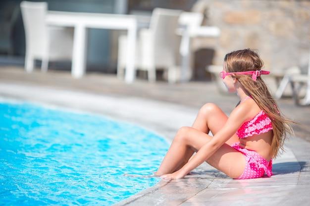 La piccola ragazza felice nella piscina all'aperto gode della sua vacanza