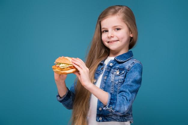 La piccola ragazza graziosa in giacca di jeans con lunghi capelli castani tiene un hamburger