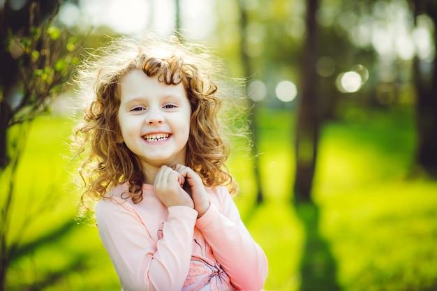 La piccola ragazza piena di sole sta sorridendo.