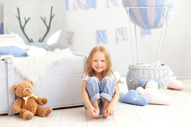 La piccola ragazza sorridente in jeans si siede sul pavimento con un pallone decorativo. il bambino gioca nella stanza dei bambini.