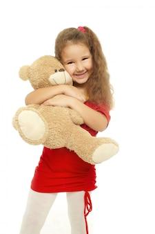 La piccola ragazza sorridente sta abbracciando con l'orso in vestito rosso isolato su bianco