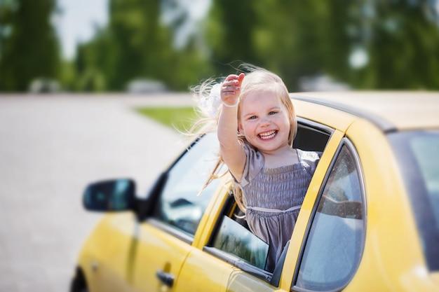 La piccola ragazza sorridente sta attaccando la sua testa fuori il finestrino della macchina e sta esaminando la macchina fotografica