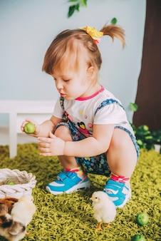 La piccola ragazza sta giocando con il pollo sull'erba del tappeto vicino al muro con l'albero