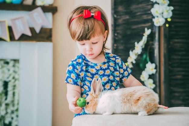 La piccola ragazza sta giocando con mele e coniglio