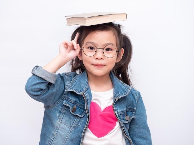 La piccola ragazza sveglia asiatica che indossa gli occhiali e ha messo il libro sulla sua testa