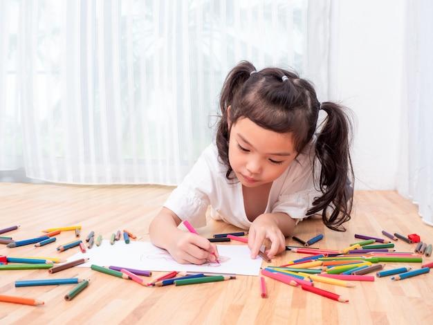 La piccola ragazza sveglia asiatica che si trova sul pavimento ed utilizza il fumetto del disegno a matita di colore su libro bianco.