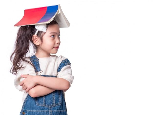 La piccola ragazza sveglia asiatica ha messo il libro sulla testa e sullo sguardo. vista laterale del bambino adorabile prescolare con il libro