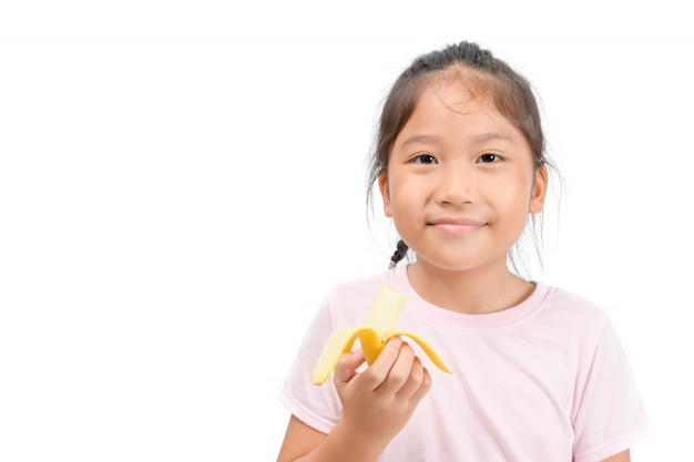 La piccola ragazza sveglia asiatica mangia la banana isolata su bianco