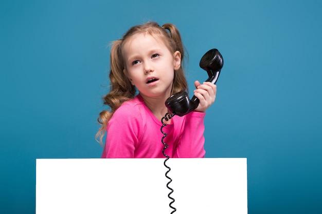 La piccola ragazza sveglia attraente in camicia rosa con la scimmia ed i pantaloni blu tengono il manifesto vuoto e parla un telefono