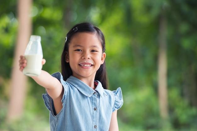 La piccola ragazza sveglia dell'asia sta bevendo il latte in bottiglia