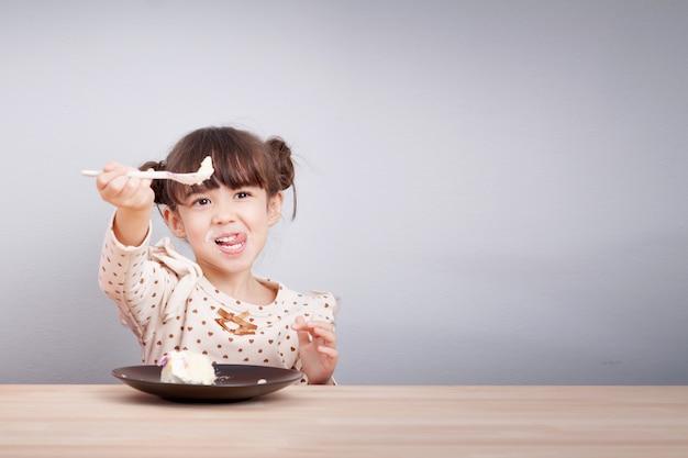 La piccola ragazza sveglia felice della corsa mista gode di di mangiare il dolce con la faccia di smiley