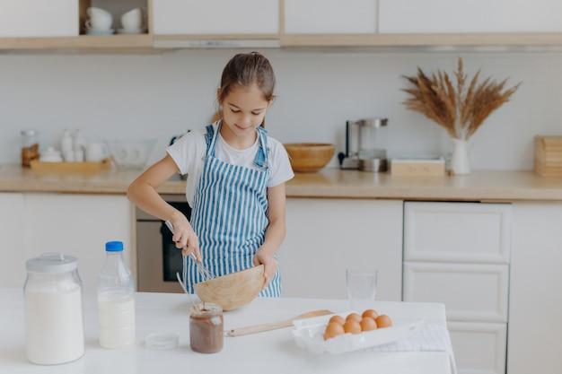 La piccola ragazza sveglia indossa un grembiule a strisce, sbatte gli ingredienti in una ciotola, prepara la pasta, insegna a cucinare