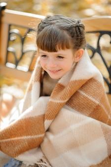 La piccola ragazza sveglia si siede su una panchina nel parco di autunno. la ragazza si rifugiò per scaldarsi. tempo d'autunno.