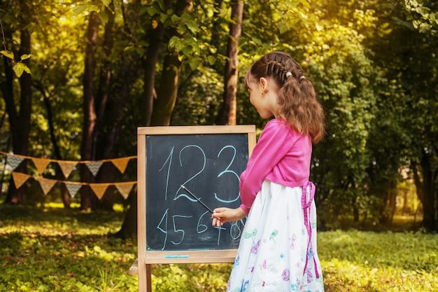 La piccola scolara insegna ai numeri vicino alla lavagna. di nuovo a scuola. il concetto di educazione, scuola