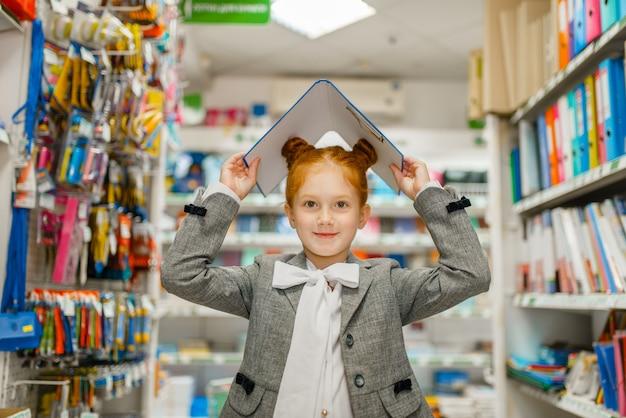 La piccola scolara tiene le cartelle sopra la sua testa in cartoleria. bambino femminile acquisto di forniture per ufficio in negozio, scolaro in supermercato