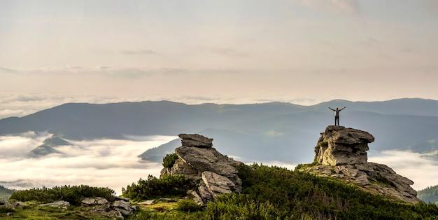 La piccola siluetta del turista con le armi alzate su formazione rocciosa sulla valle della montagna ha riempito di nuvole e nebbia gonfie bianche e coperte di pendii di montagna sempreverdi della foresta nell'ambito del chiaro fondo del cielo.