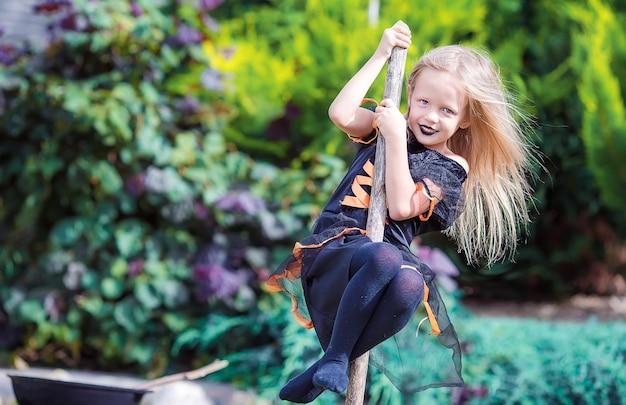 La piccola strega felice si diverte all'aperto ad halloween. dolcetto o scherzetto.