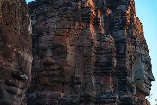 La pietra affronta in bayon, il tempio di angkor thom, la destinazione di viaggio cambogia
