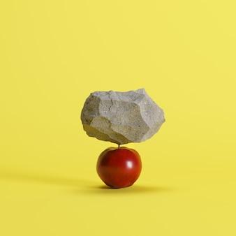 La pietra ha messo sopra una mela su fondo giallo