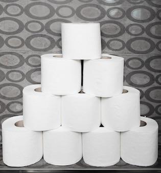 La pila del primo piano di carta igienica rotola sullo scaffale
