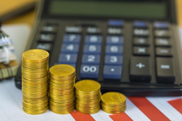 La pila della moneta e la carta finanziaria del grafico rivestono con il calcolatore sulla tavola