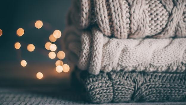 La pila di maglioni e luci garland tricottati accoglienti su fondo di legno