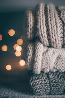 La pila di maglioni e luci garland tricottati accoglienti su fondo di legno.