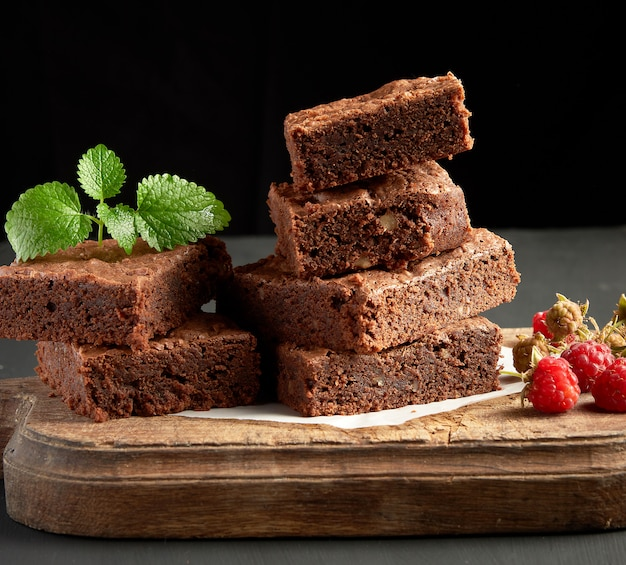 La pila di pezzi quadrati al forno di brownie al cioccolato agglutina sul tagliere di legno marrone
