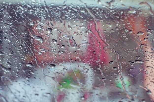 La pioggia cade l'acqua sul fondo di superficie della finestra di automobile, vista dall'auto che ora piove fondo