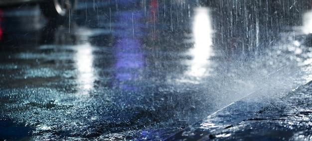 La pioggia dura cade di notte con le auto sfocate. messa a fuoco selettiva.