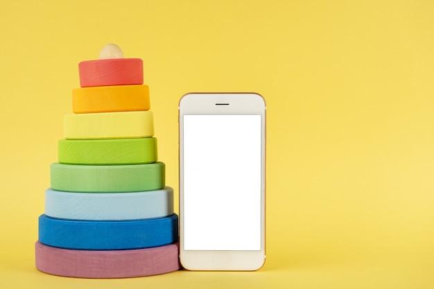 La piramide multicolore del bambino e il telefono cellulare deridono su su fondo giallo