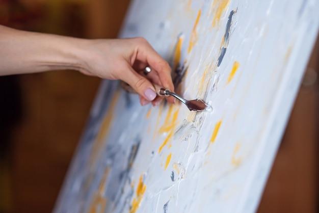 La pittura astratta creata con mastice e vernice gialla.