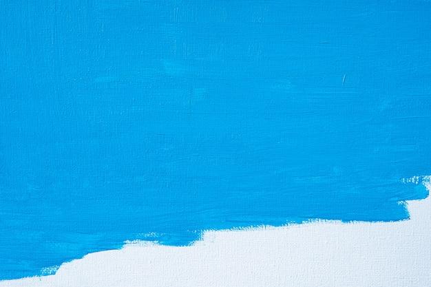 La pittura blu dell'estratto di colore con un pennello e le trame di colore ad olio colorano le linee del disegno di olio sul fondo bianco della tela