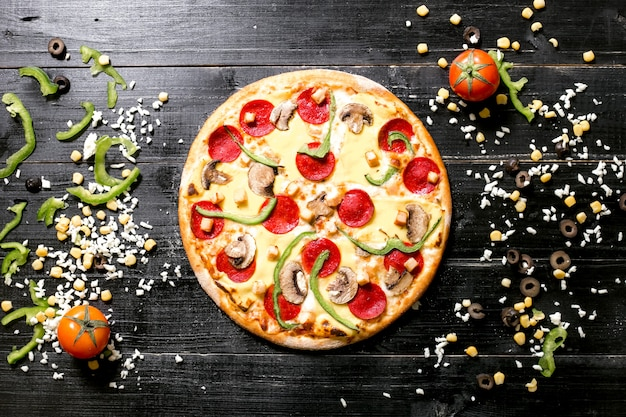 La pizza ai peperoni con funghi accanto al formaggio spruzza il peperone del pomodoro verde oliva del cereale