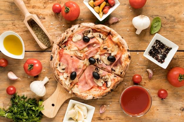 La pizza appena sfornata è circondata da ingredienti sopra una scrivania strutturata
