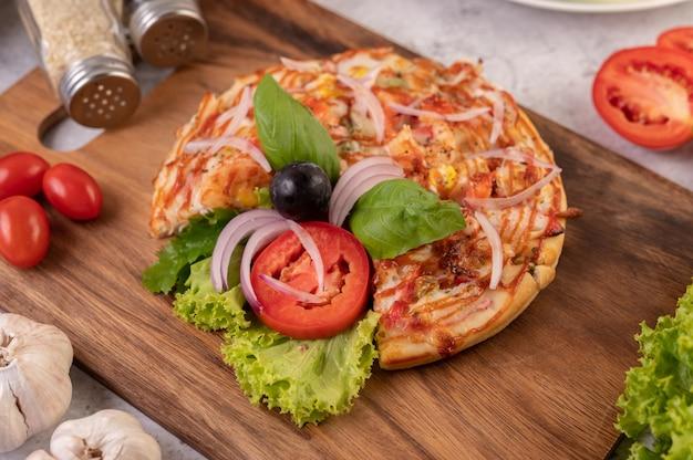 La pizza è in un vassoio di legno condita con cipolle rosse, uva nera, pomodori e lattuga.