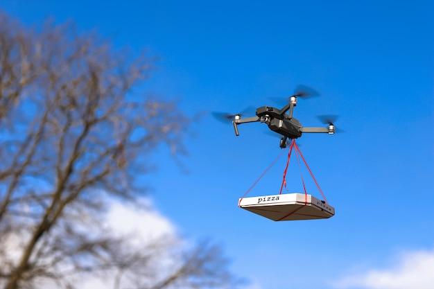 La pizza è legata al quad. consegna pizza con drone
