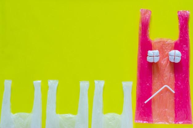 La plastica rosa incastona come un'espressione infelice con la cannuccia di plastica per smettere di usare pacchi ambientali ostili.