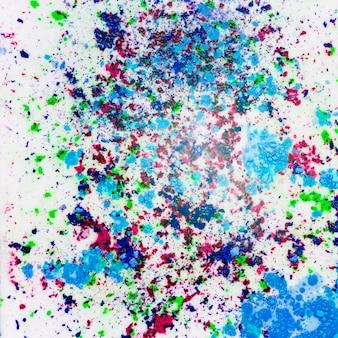 La polvere colorata di holi schizza su fondo bianco