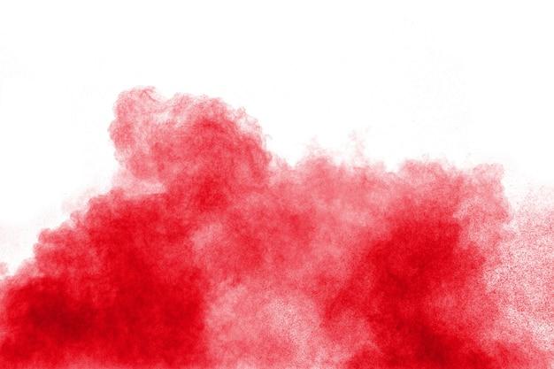 La polvere rossa astratta schizza su fondo bianco. esplosione di polvere rossa