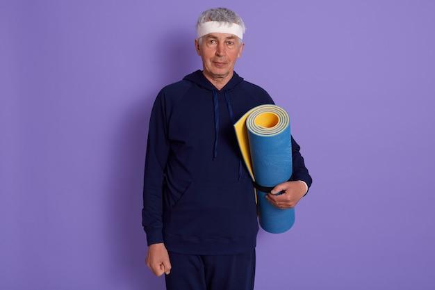 La posa matura dell'interno dell'uomo isolata sul lillà con la stuoia di yoga in mani, il vestito di sport d'uso maschio e la fascia capa, il tipo senior posa dopo l'allenamento sportivo. fitness, concetto di vecchiaia attiva.