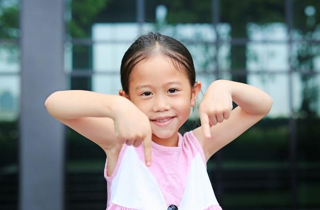 La posizione asiatica della bambina che indica il suo indice giù con il piccolo sorriso.