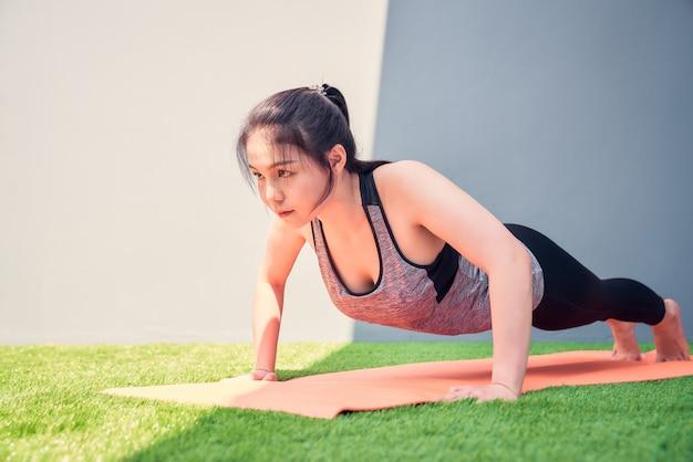 La pratica asiatica della donna spinge verso l'alto su una stuoia arancio di addestramento su erba verde. concetto di benessere.